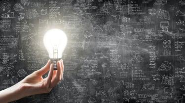 A hand holding a lit lightbulb against scribbles on a blackboard