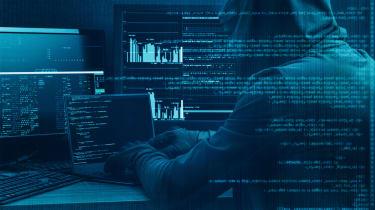 Darkened image of a hacker wearing a hoodie using computing equipment