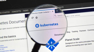 A magnifying glass held over a kubernetes logo on a computer screen