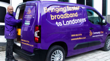 """A Community Fibre employee stands next to the company van with the slogan """"Bringing faster broadband to Londoners"""""""