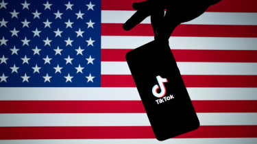 Smartphone with TikTok opening screen on it in front of an American flag