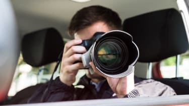 A man taking a photo with a telephoto lens