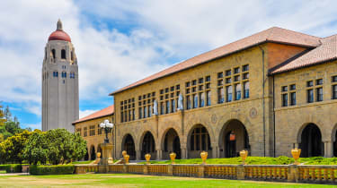 Stanford University's front lawn and main building on a sunny day, with the bell tower in the background