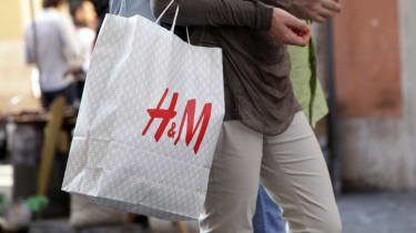 A shopper holding an H&M bag full of items in a busy high street