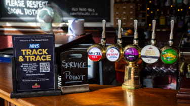 A Test and Trace sign next to beer pumps in a hospitality venue