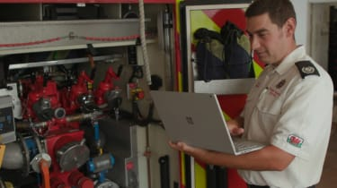 A Welsh firefighter working on a Microsoft laptop while standing