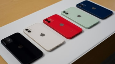 Five iPhone 12 models in black, white, red, green, and blue displayed on a table