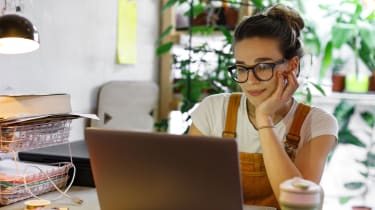 Woman in dungarees sat in a home office, smiling slightly while she looks at her laptop.