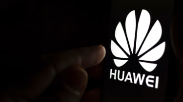 A finger about to press a Huawei logo in a dark room