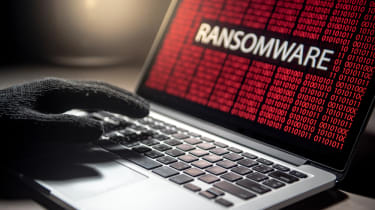 Male hacker hand on laptop computer keyboard with red binary screen of ransomware attack