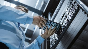 A person putting a storage device into a rack in a data centre