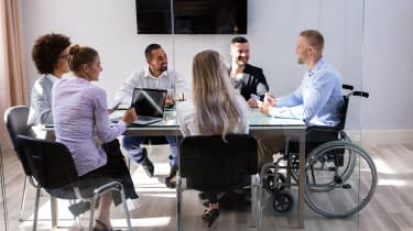 A multi-ethnic, mixed gender team of six colleagues sitting round a meeting room table listening to one member speak, who is in a wheelchair