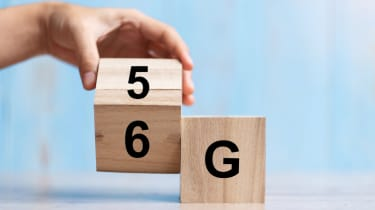 A hand changing a wooden block from 5G to 6G