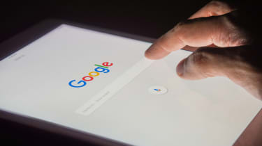 A hand using the Google search bar on a tablet computer