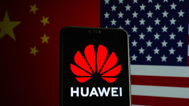 Huawei logo on a smartphone and flags of China and US on the blurred background