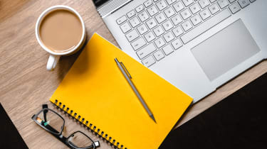 A laptop, yellow notebook, pen, cup of tea and pair of glasses laid out on a desk