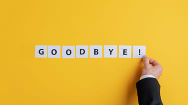 "A businessman's hand placing white squares with black lettering spelling out ""Goodbye!"" on a yellow background"