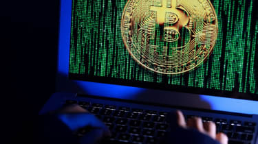 Cyber criminals in a dark room using a monitor with the Bitcoin logo shown