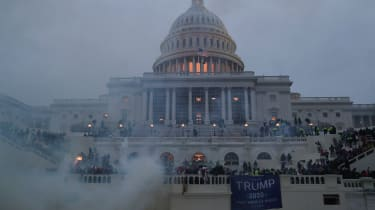 Capitol building with smoke surrounding it and rioters on it