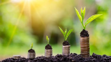 five stacks of coins standing on soil with progressively more mature seedlings on top of them, symbolising investment and growth