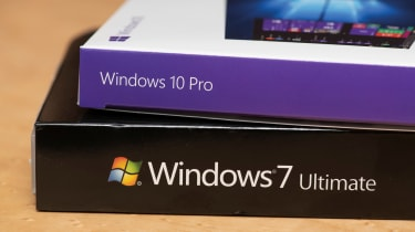 A Windows 10 Pro box lying on top of a Windows 7 Ultimate box, which is sitting on a table