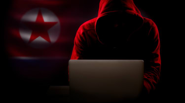 North Korea hacker in the dark with the country's flag in the background