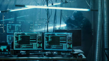 Cyber warfare depicted by code on two monitors with a soldier in background