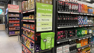 """A container of Amazon Fresh bags for life at the end of an aisle below a sign saying """"Choose what you like, bag as you shop, just walk out! We'll email you a receipt"""""""