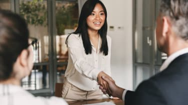 A young job candidate being greeted at the interview by handshake