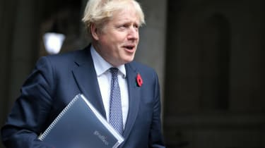 The prime minister, Boris Johnson, holding a folder