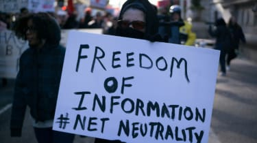"""Protestor holding sign reading """"Freedom of information, Net Neutrality"""", at a rally for net neutrality on the streets of Philadelphia in January 2018."""