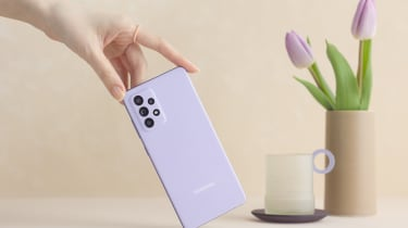 A purple model of the Samsung Galaxy A52 5G with tulips and cup in background