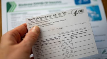 Woman's hand holding a COVID-19 vaccination card
