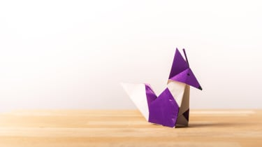 An origami purple fox on a wooden surface