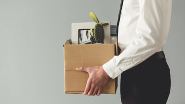 Cropped image of businessman in formal wear holding a box with his stuff