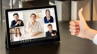 A group of young colleagues welcoming a new team member via video call