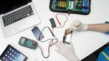 An independen technician repairing an iPhone on a desk alongside other Apple products