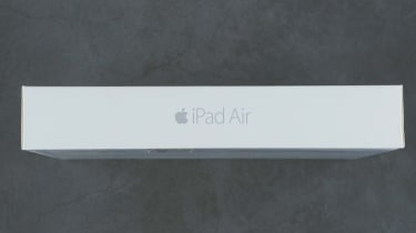Box containing silver Apple iPad Air 2, 6th generation of the iPad, on grey background