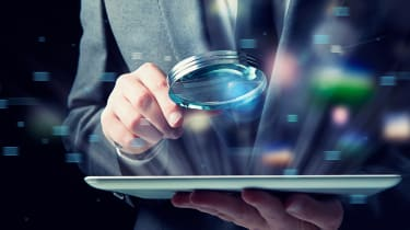 Abstract image of a man holding a magnifying glass over a tablet