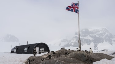 A hut at Port Lockroy British Antarctic Survey base with penguins and a union flag in the foreground