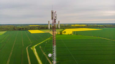 Aerial view video of telecommunication tower in the countryside farming fields with 4G, 5G cellular network antennas.