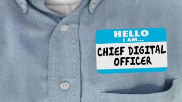A man in a shirt wearing a 'Hello, I am a chief digital officer' sticker