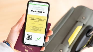 Overhead view of an human hand holding a passport and a smart phone with a digital illustration of a certificate of vaccination against the Covid-19 disease.