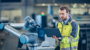 A male engineer reprogramming a robotic arm in a factory using a laptop