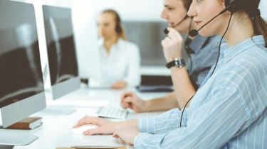 Call center employees on their headsets in front of computers