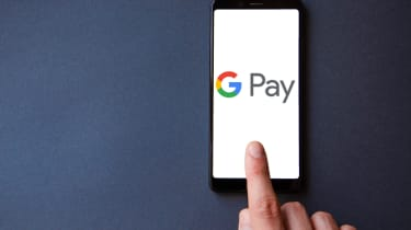 Google Pay logo on a smartphone with a hand hovering above