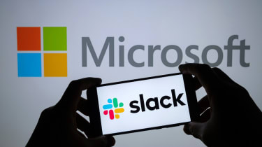 A person holding a smartphone with a Slack logo against a larger Microsoft logo
