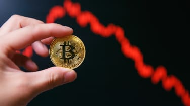 A graphic interpretation of the decrease in the cost of bitcoin, with a hand holding a coin with bitcoin logo