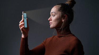 Woman holding a smartphone up to her face so the biometric scanner can read her face