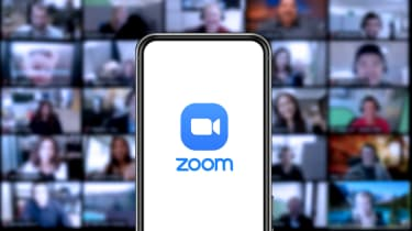 Zoom's logo on a mobile phone with screens of people in the background